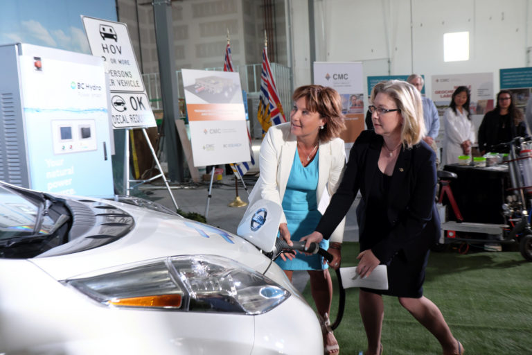 Premier Clark and Minister Polak plug in an electric car at the climate plan announcement