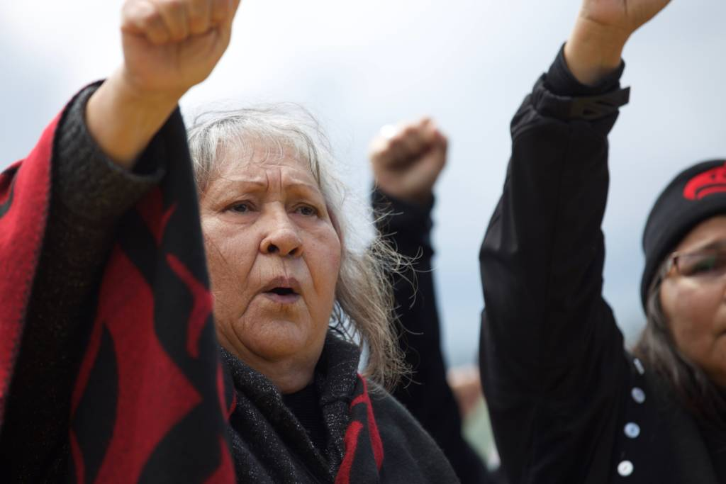 Indigenous woman with fist raised