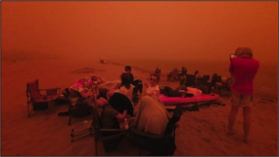 People on a beach huddling from smoke and fire.
