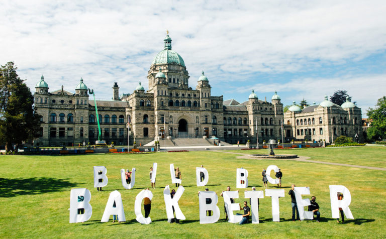Dogwood volunteers holding five foot letters that spell out 'Build BC Back Better' on the Legislature lawn with the Legislature building in the background.