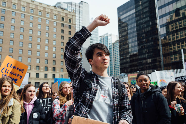 Teen climate protestor stands in a crown with a raised fist