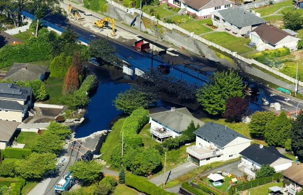 Aerial image of Trans Mountain Pipeline oil spill in Burnaby, covers entire intersection, yards and is next to houses.