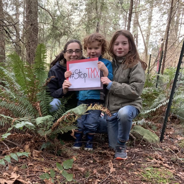 A family holds a sign saying #StopTMX